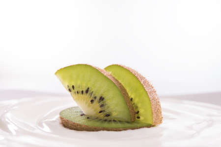 Plain yogurt with fresh kiwi fruit on top in bowl isolated on white Banco de Imagens