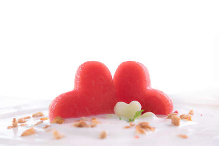 Plain yogurt with fresh heart shape watermelon on top in bowl isolated on white Banco de Imagens