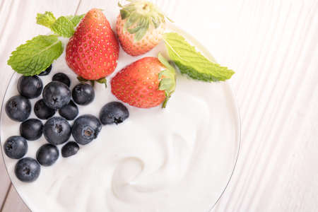 Plain yogurt with fresh berry fruits on top in bowl on the table Banco de Imagens