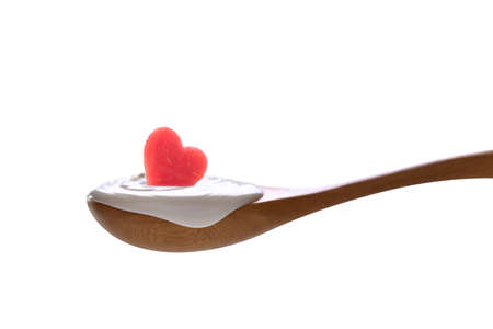 Plain yogurt on a spoon with fresh heart shape watermelon on top isolated on white