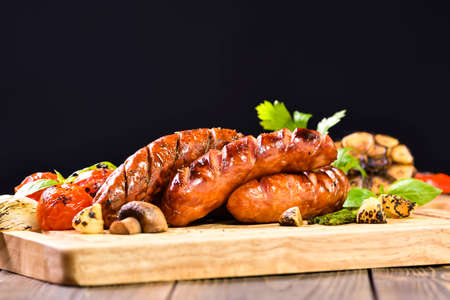 Grilled sausages and various vegetables on chopping wood Banco de Imagens