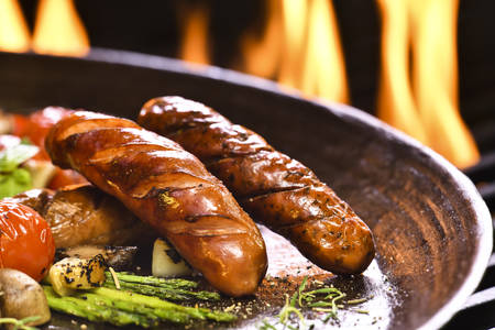 Grilled sausages and various vegetables  in iron pan Banco de Imagens