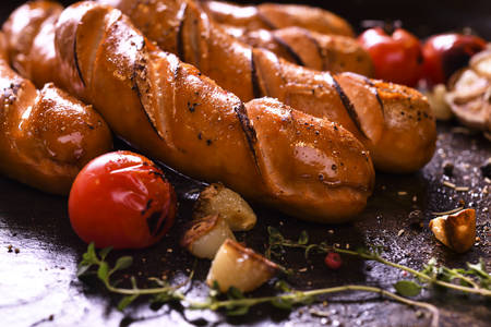 Grilled sausages and various vegetables  in iron plate Banco de Imagens