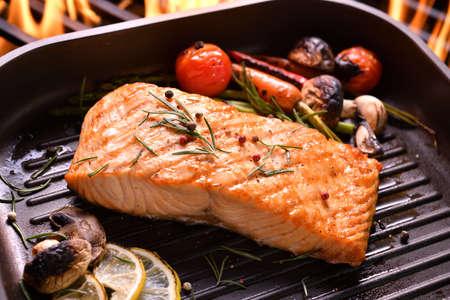Poisson saumon grillé avec divers légumes sur la poêle sur le gril enflammé