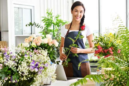 Joven empresaria asiática / dueña de una tienda / floristería de una pequeña tienda de flores