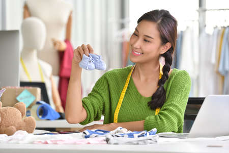 Young Asian woman entrepreneur  fashion designer for baby clothes working in studio