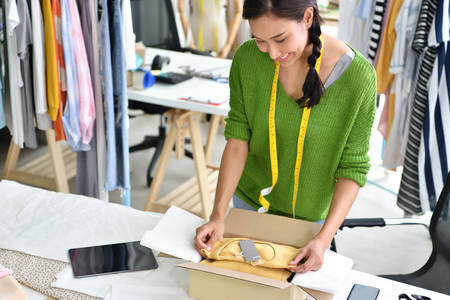 Young Asian woman entrepreneur  fashion designer working in studio and packing and sending product