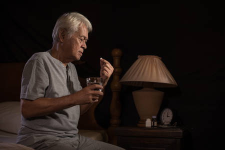 Depressed senior person sitting in bed cannot sleep from insomnia and taking medication