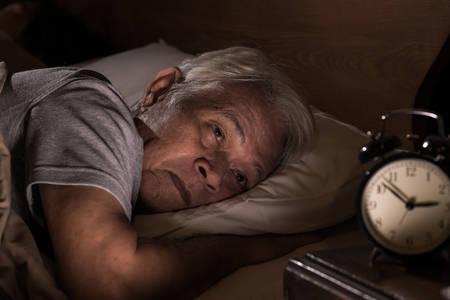 Przygnębiony starszy mężczyzna leżący w łóżku nie może spać z powodu bezsenności