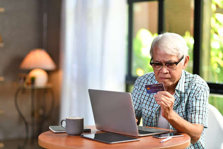 Asian senior man looking confuse when using credit for online shopping