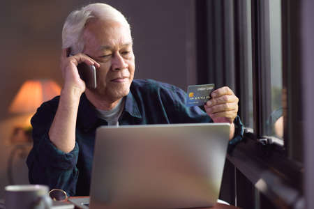 Happy Asian senior man using credit card for online shopping