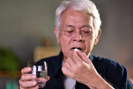 Asian senior man taking pills at home