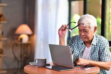 Asian senior man using laptop in living room at home