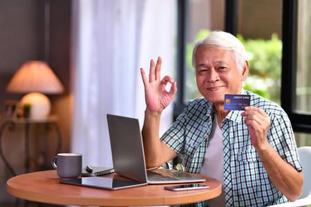 Asian senior man using credit card for online shopping Stockfoto