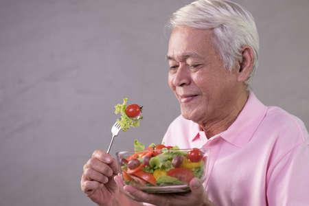 Asian senior man in joyful postures with hand holding salad bowl