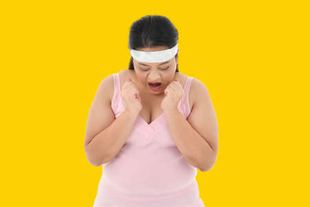 Overweight Asian woman looking shocked to see the weight on the scale Stockfoto
