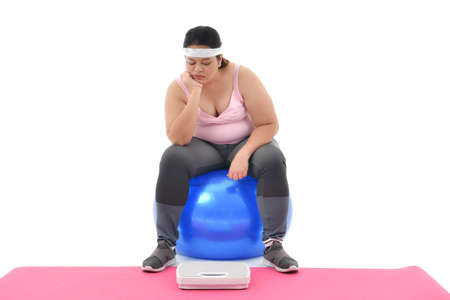 Overweight Asian woman sitting on gym ball looking boringly at the scale isolated on white background Stockfoto