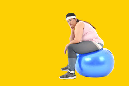 Overweight Asian woman sitting on a gym ball looking bored Stockfoto