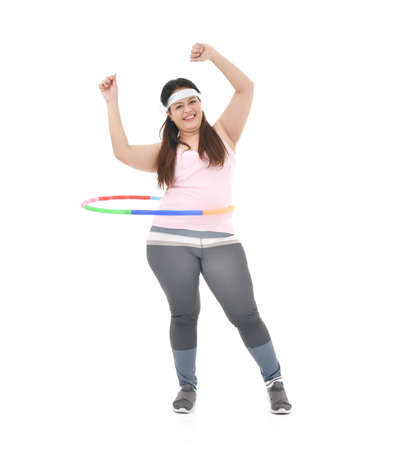 Overweight Asian woman exercising with a hula-hoop isolated on white background