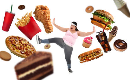 Overweight Asian woman fighting off junk food isolated on white background Фото со стока