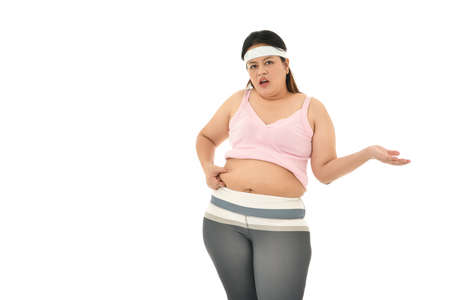 Overweight Asian woman pinching belly fat isolated on white background Stockfoto