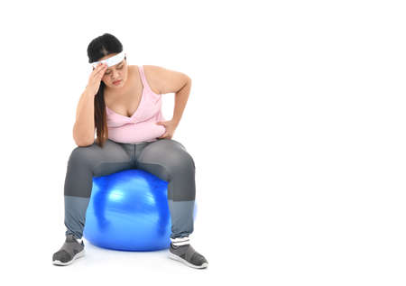 Overweight Asian woman sitting on a gym ball and pinching belly fat isolated on white background Stockfoto