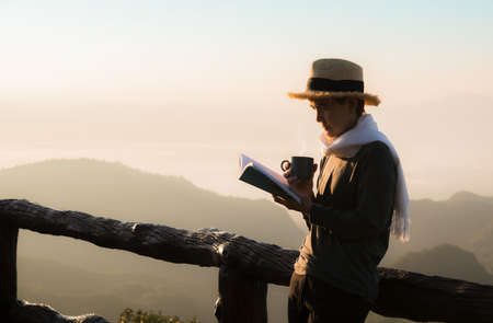 Asian woman standing and reading book at beaitiful natural view