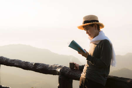 Asian middle aged woman standing and reading book at beaitiful natural view