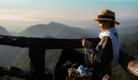 Middle aged Asian woman sitting on the bench and knitting for winter Christmas at beaitiful natural view Stockfoto
