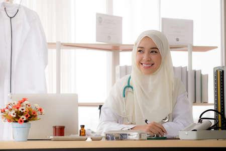 Porträt einer charmanten muslimischen Ärztin, die am Schreibtisch arbeitet und lächelt
