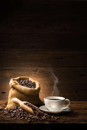 Taza de café con humo y granos de café en madera vieja