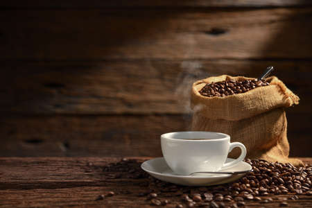 Cup of coffee with smoke and coffee beans on old wooden
