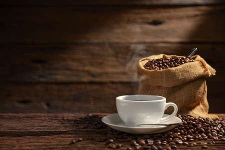 Filiżanka kawy z dymem i ziarnami kawy na starym drewnianym?