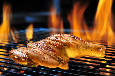 Grill bbq roast chicken thigh on the flaming grill Banco de Imagens