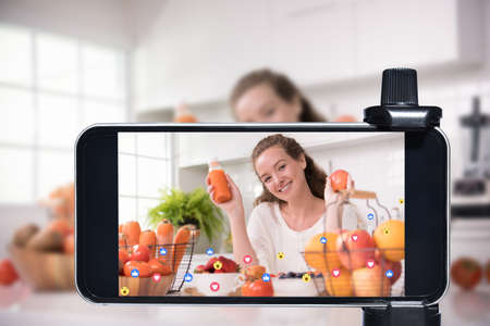Young female blogger and vlogger and online influencer live streaming a cooking show on social media using a smartphone