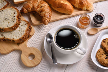 Top view of cup of coffee with breads or bun, croissant and bakery on white wooden table