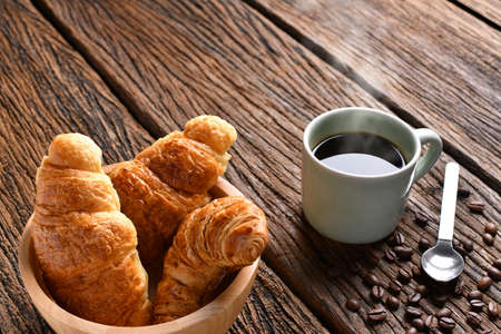 Cup of coffee with coffee beans and croissant on wooden table