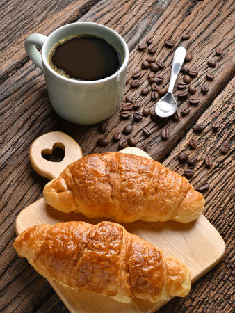 A cup of coffee with coffee beans and croissant on wooden table Standard-Bild