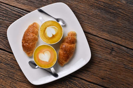 Top view cup of coffee latte and croissant on old wooden table Standard-Bild