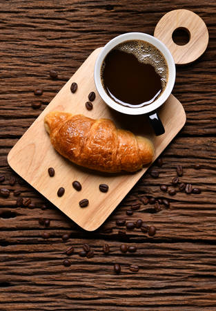Top view a cup of coffee with coffee beans and croissant on wooden table