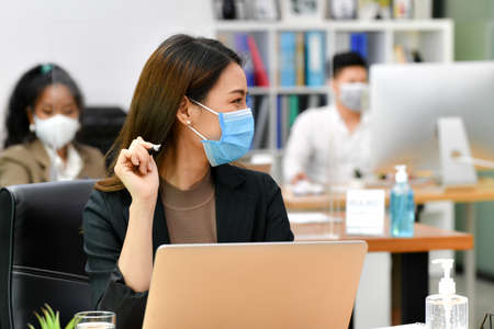 Portrait of Asian woman office worker wearing face mask working in new normal office and doing social distancing during corona virus covid-19 pandemic