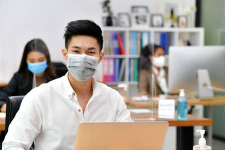 Portrait of Asian man office worker wearing face mask working in new normal office and doing social distancing during corona virus covid-19 pandemic
