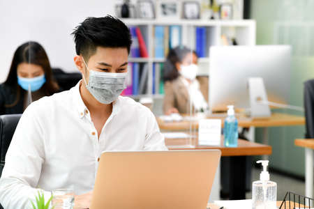 Portrait of Asian man office worker wearing face mask working in new normal office and doing social distancing during corona virus covid-19 pandemic Banco de Imagens