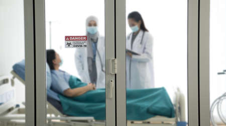 Asian female doctor wearing protective gears examination and treating patient in a hospital room with selective focus on door sticker