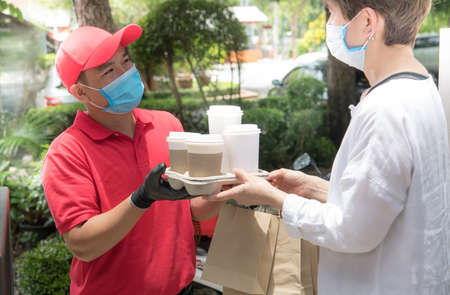 Asian delivery man wearing face mask and gloves in red uniform delivering bag of food and drink to recipient during COVID-19 outbreak
