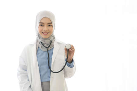 Portrait of Asian muslim female doctor showing stethoscope to camera on white background Imagens
