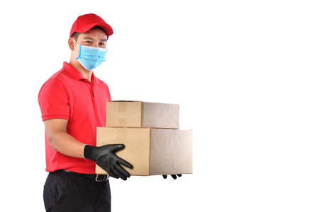 Happy young Asian delivery man in red uniform, medical face mask, protective gloves carry cardboard box in hands isolated on white background. Delivery guy give parcel shipment. Safe delivery Imagens