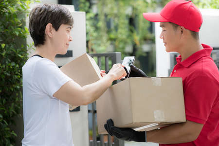 Asian delivery man in red uniform delivering parcel box to woman recipient at home with recipient sign to receive the package on smart device
