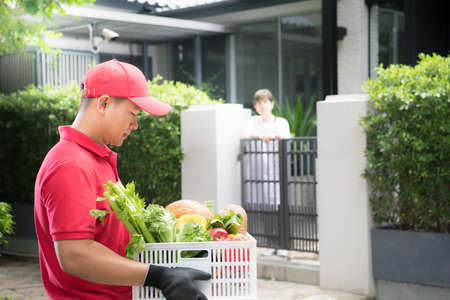 Asian delivery man in red uniform delivering  groceries box of food, fruit, vegetable and drink to woman recipient at home Imagens