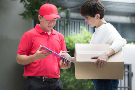 Asian delivery man in red uniform delivering parcel box to woman recipient at home with recipient sign to receive the package on clip board Imagens